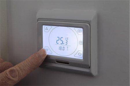 Person adjusting digital thermostat Stock Photo - Premium Royalty-Free, Code: 614-06402975