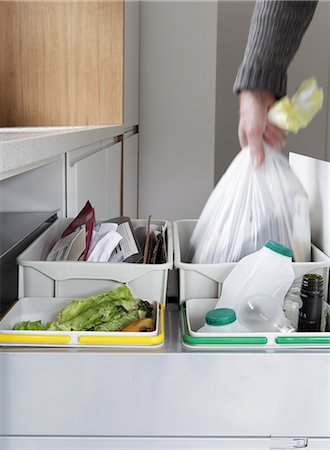 Person removing rubbish bag from waste and recycling drawer Stock Photo - Premium Royalty-Free, Code: 614-06402987