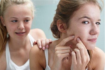 spotted - Girl squeezing a spot, friend with hand on shoulder Stock Photo - Premium Royalty-Free, Code: 614-06403018