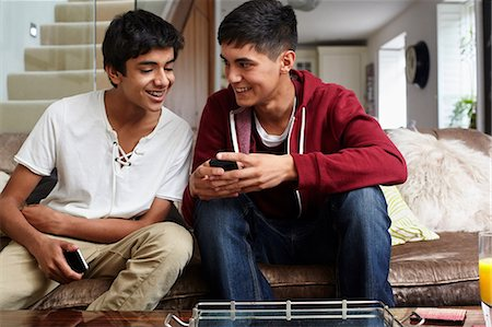 Teenage boys looking at cellphone Stock Photo - Premium Royalty-Free, Code: 614-06403027