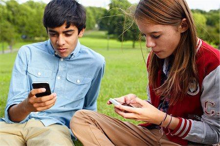 Teenage boy and girl using smartphones Stock Photo - Premium Royalty-Free, Code: 614-06403087