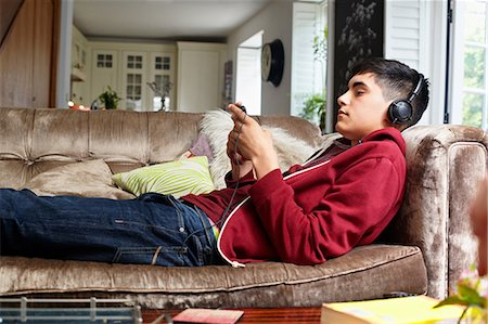 east indian (male) - Teenage boy on sofa, listening to music Stock Photo - Premium Royalty-Free, Code: 614-06403080