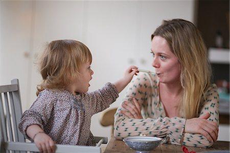 Daughter spoon feeding mother Stock Photo - Premium Royalty-Free, Code: 614-06442296