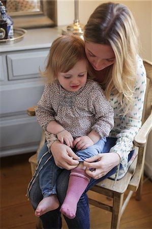 Mother helping daughter put on socks Stock Photo - Premium Royalty-Free, Code: 614-06442307