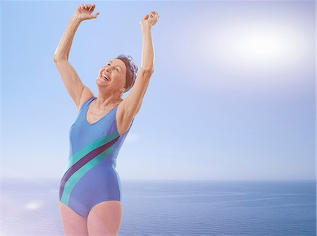 Senior woman wearing swimsuit cheering with arms raised Stock Photo - Premium Royalty-Free, Code: 614-06442314