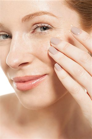 Woman applying eye gel Stock Photo - Premium Royalty-Free, Code: 614-06442380