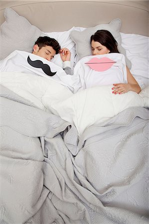 Couple in bed with lips and moustache Stock Photo - Premium Royalty-Free, Code: 614-06442402