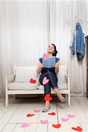 Woman reading book with heart shapes Stock Photo - Premium Royalty-Free, Code: 614-06442415