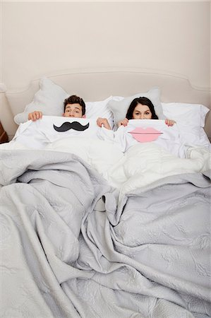 Couple in bed with lips and moustache Stock Photo - Premium Royalty-Free, Code: 614-06442440