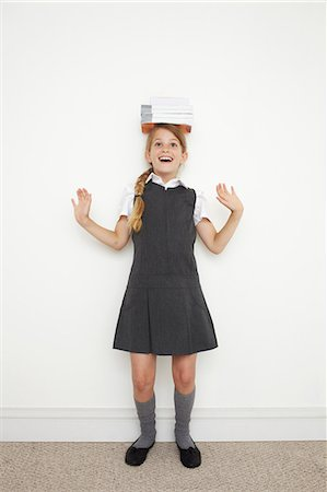 school girl uniforms - Schoolgirl balancing books on her head Stock Photo - Premium Royalty-Free, Code: 614-06442480