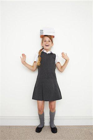 school girl uniforms - Schoolgirl balancing books on her head Stock Photo - Premium Royalty-Free, Code: 614-06442480