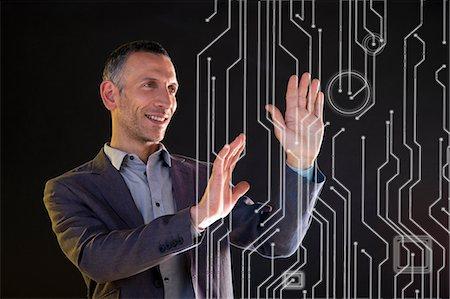 futuristic - Businessman touching virtual circuit board symbols Stock Photo - Premium Royalty-Free, Code: 614-06442501