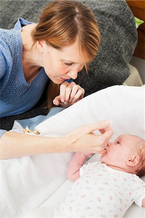 sucking - Mother comforting newborn daughter Stock Photo - Premium Royalty-Free, Code: 614-06442535
