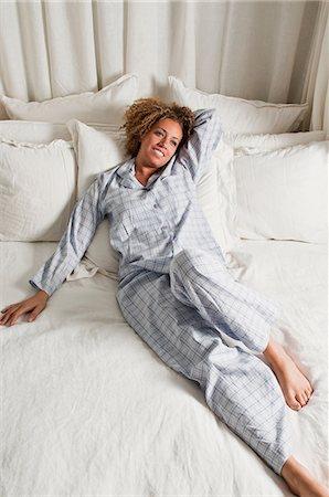 Woman wearing pyjamas reclining in bed Stock Photo - Premium Royalty-Free, Code: 614-06442623