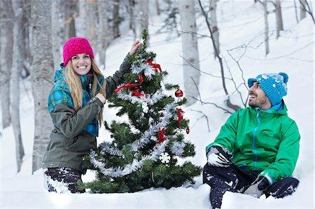 snow christmas tree white - Couple decorating christmas tree Stock Photo - Premium Royalty-Free, Code: 614-06442677