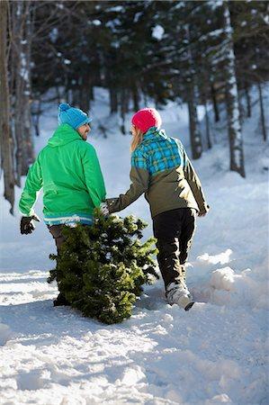 snow christmas tree white - Couple dragging christmas tree through snow Stock Photo - Premium Royalty-Free, Code: 614-06442709