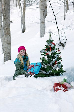 snow christmas tree white - Woman sitting by christmas tree with gift Stock Photo - Premium Royalty-Free, Code: 614-06442703