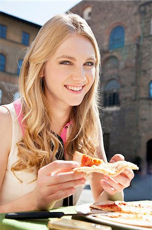 Young woman at restaurant outdoors with slice of pizza Stock Photo - Premium Royalty-Free, Code: 614-06442732
