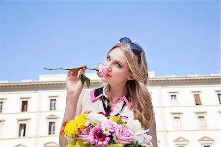 Young woman smelling rose from bouquet of flowers Stock Photo - Premium Royalty-Free, Code: 614-06442744