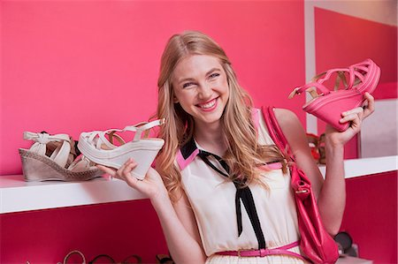 pink - Happy young woman holding shoes in store Stock Photo - Premium Royalty-Free, Code: 614-06442745