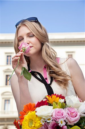 Young woman smelling rose from bouquet of flowers, eyes closed Stock Photo - Premium Royalty-Free, Code: 614-06442748