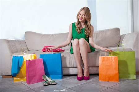 Young woman sitting on sofa with shopping bags Stock Photo - Premium Royalty-Free, Code: 614-06442790