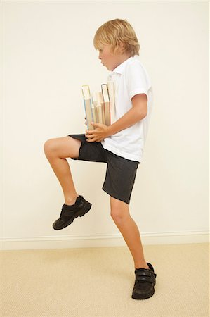 Schoolboy carrying stack of school books Stock Photo - Premium Royalty-Free, Code: 614-06442823