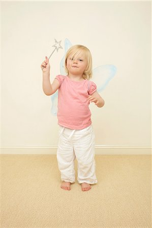Toddler wearing wings, holding wand Stock Photo - Premium Royalty-Free, Code: 614-06442834