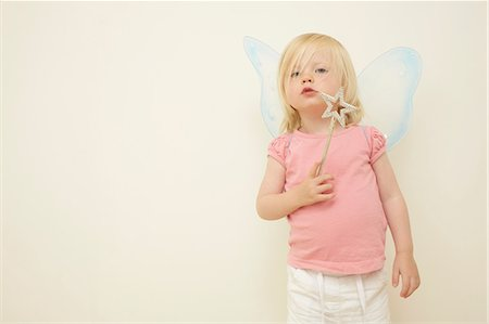 Toddler wearing wings, holding wand Stock Photo - Premium Royalty-Free, Code: 614-06442832