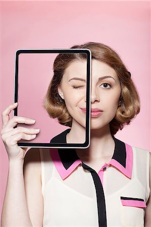 Woman covering half her face with digital tablet Stock Photo - Premium Royalty-Free, Code: 614-06442854