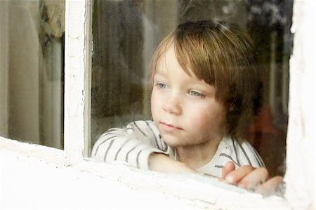 Little boy looking through window Stock Photo - Premium Royalty-Free, Code: 614-06442850