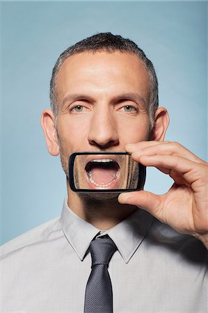 Man with smartphone over mouth Stock Photo - Premium Royalty-Free, Code: 614-06442863