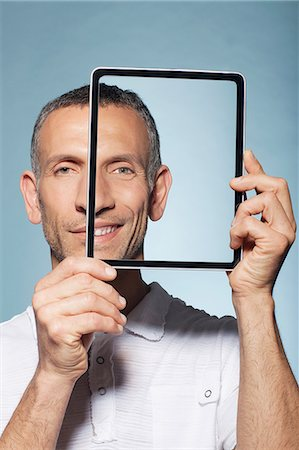 Man covering half his face with digital tablet Stock Photo - Premium Royalty-Free, Code: 614-06442882