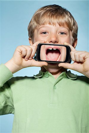 Boy holding smartphone over mouth Stock Photo - Premium Royalty-Free, Code: 614-06442908