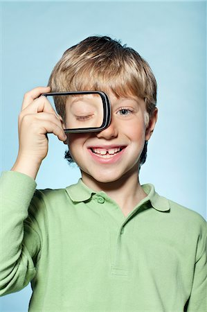Boy holding smartphone over eye Stock Photo - Premium Royalty-Free, Code: 614-06442909