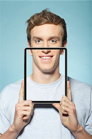 Man covering half his face with digital tablet Stock Photo - Premium Royalty-Free, Code: 614-06442916