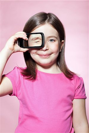 pink - Girl holding smartphone over eye Stock Photo - Premium Royalty-Free, Code: 614-06442911