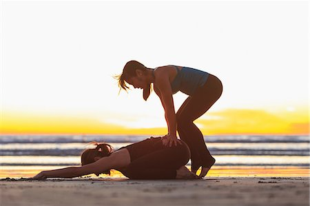 southern california - Instructor helping woman into yoga pose on beach Stock Photo - Premium Royalty-Free, Code: 614-06442923