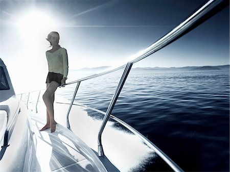 Woman standing on deck of yacht Stock Photo - Premium Royalty-Free, Code: 614-06442937