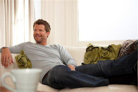 Man relaxing on sofa Stock Photo - Premium Royalty-Free, Code: 614-06442992