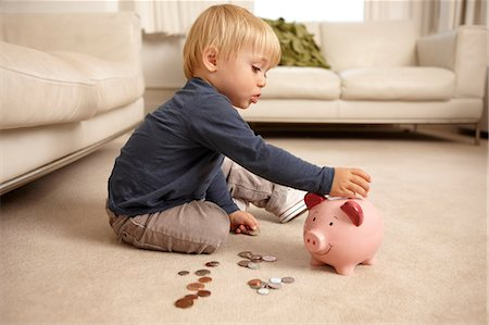savings - Boy putting coins in piggy bank Stock Photo - Premium Royalty-Free, Code: 614-06443000