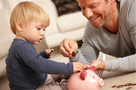 savings - Father and son putting coins in piggy bank Stock Photo - Premium Royalty-Free, Code: 614-06443002