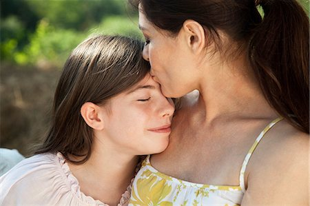 preteen kissing - Portrait of mother kissing daughter on forehead Stock Photo - Premium Royalty-Free, Code: 614-06443070