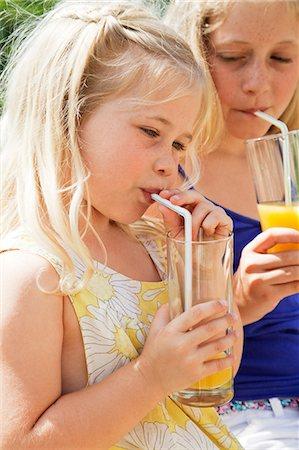 sucking - Two girls drinking orange juice Stock Photo - Premium Royalty-Free, Code: 614-06443084