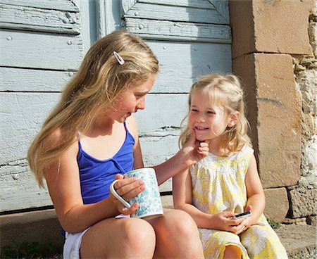 preteen girls faces photo - Two sisters, one touching others face Stock Photo - Premium Royalty-Free, Code: 614-06443081