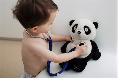 Little boy using stethoscope on panda toy Stock Photo - Premium Royalty-Free, Code: 614-06443110