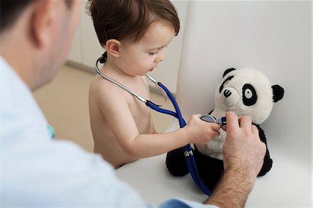 Little boy and doctor using stethoscope on panda toy Stock Photo - Premium Royalty-Free, Code: 614-06443111