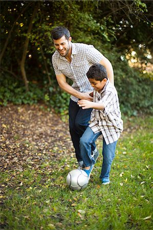Father and son playing soccer together Stock Photo - Premium Royalty-Free, Code: 614-06536728