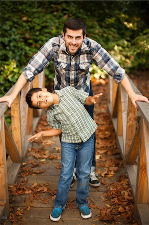 Father and son playing on wooden bridge Stock Photo - Premium Royalty-Free, Code: 614-06536735