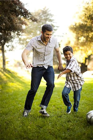 family  fun  outside - Father and son playing soccer together Stock Photo - Premium Royalty-Free, Code: 614-06536730